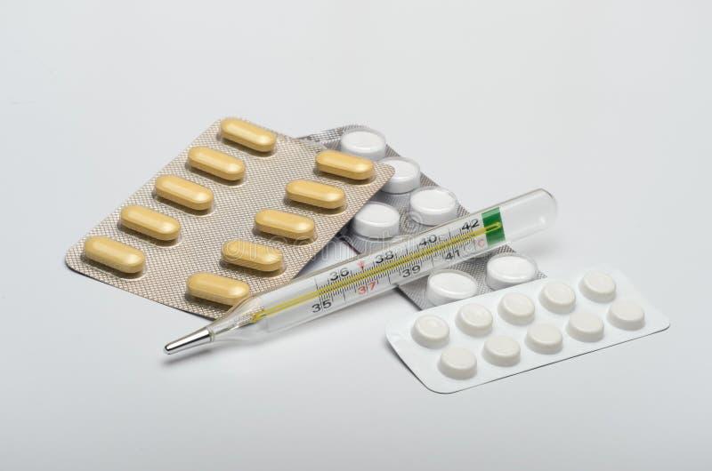 Medicinas con un termómetro, tabletas contra enfermedades virales fotos de archivo