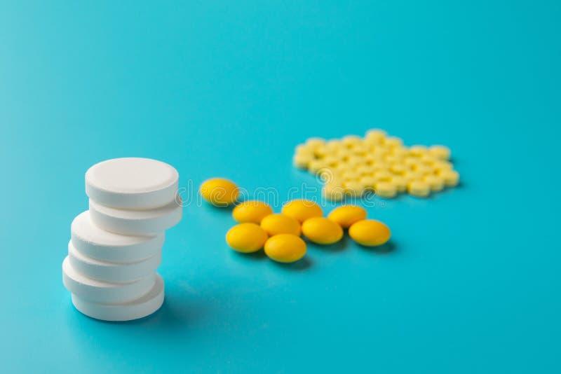 Medicinas y píldoras blancas y amarillas en fondo azul imagen de archivo