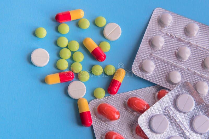 Medicinas y p?ldoras en fondo azul imagen de archivo libre de regalías