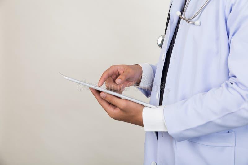 Medicindoktor som arbetar med den moderna minnestavladatoren - medicinsk te royaltyfria bilder
