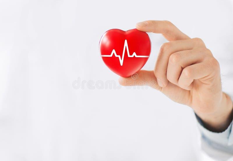 Medicindoktor som rymmer röd hjärtaform i hand med den medicinska manöverenheten för faktisk skärm för symbolsnätverksanslutning  royaltyfri foto