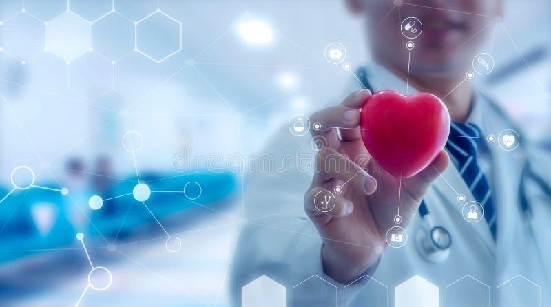 Medicindoktor som rymmer röd hjärtaform i hand med läkarundersökning royaltyfria foton