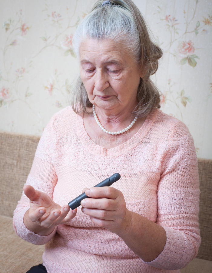 Medicine, age, diabetes, health care and people concept - senior woman with glucometer checking blood sugar level at. Home closeup stock photos