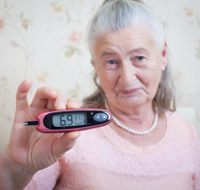 Medicine, age, diabetes, health care and people concept - senior woman with glucometer checking blood sugar level at. Home closeup royalty free stock photography