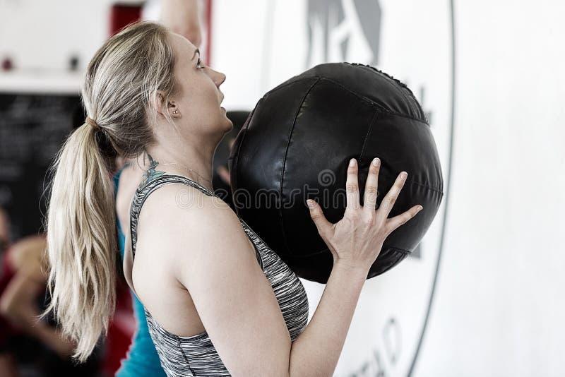 Medicine-ball de lancement de femme dans le gymnase photos stock