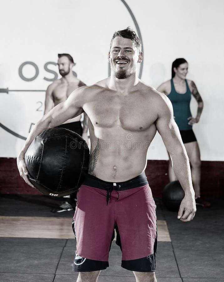 Medicine-ball de transport masculin musculaire image stock
