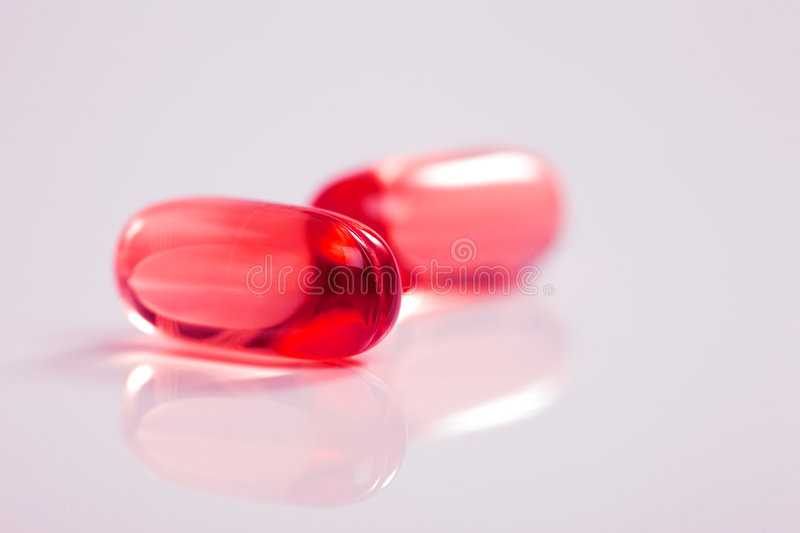 Medicine capsule. Red transparent medicine capsule on reflective table stock image