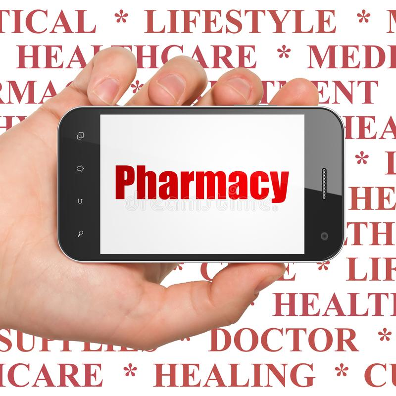 Medicine concept: Hand Holding Smartphone with Pharmacy on display royalty free stock photography