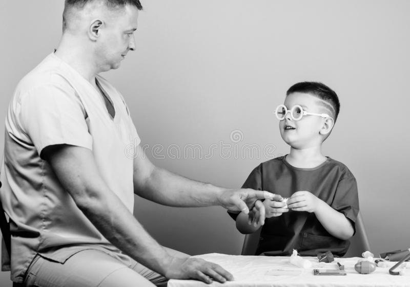 Medicine concept. Kid little doctor sit table medical tools. Health care. Medical examination. Boy cute child and his. Father doctor. Hospital worker. First aid royalty free stock photos