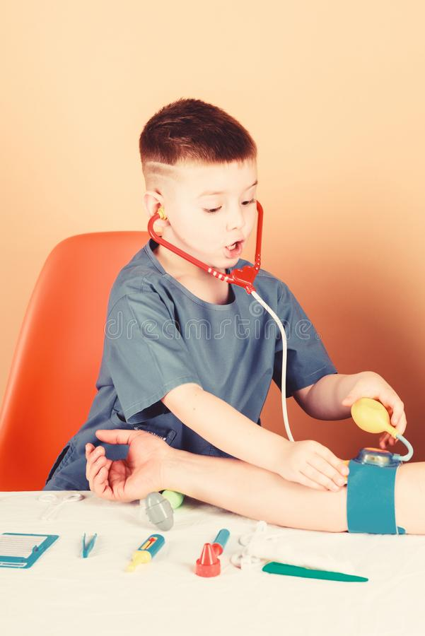 Medicine concept. Measuring blood pressure. Medical examination. Medical education. Boy cute child future doctor career. Health care. Kid little doctor sit stock photos