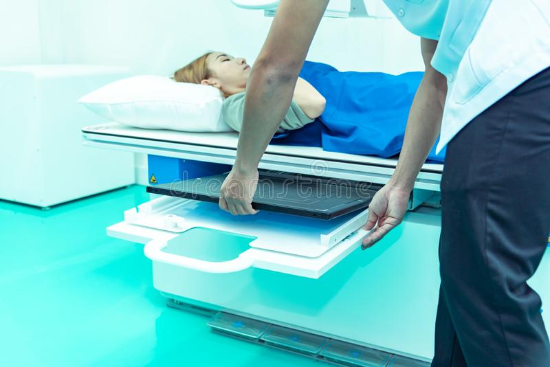 Medicine concept ,Technician Doctor male radiologist with colleague setting up machine to take female patient in x-ray room stock photos