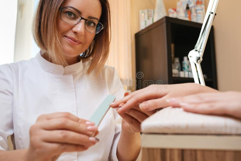 Medicine, cosmetology and manicure. A woman manicure master in glasses and a white coat does a manicure to a client in the salon. royalty free stock images