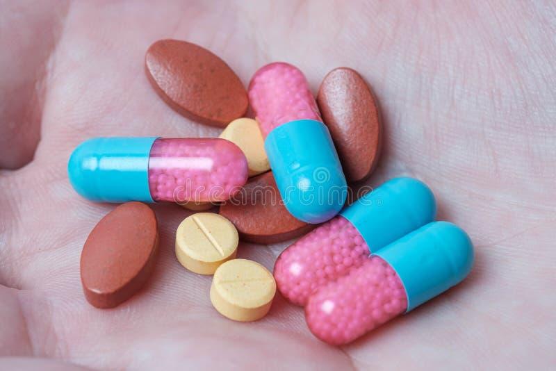 Medicine delle pillole e della capsula a disposizione con fondo rosa immagine stock libera da diritti