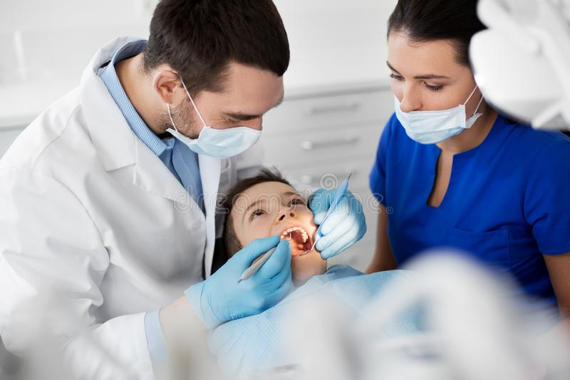 Dentist checking for kid teeth at dental clinic. Medicine, dentistry and healthcare concept - dentist with mouth mirror and probe checking for kid patient teeth stock photos