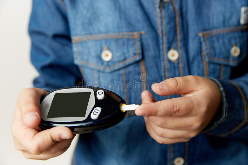 Medicine, diabetes, glycemia, health care and people concept - close up of man checking blood sugar level by glucometer royalty free stock image