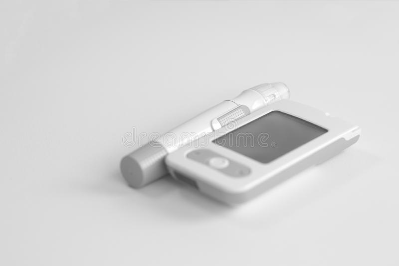 Medicine, diabetes, glycemia, health care and people concept - Glucose meter and lancet device for the diagnosis of glucose royalty free stock images