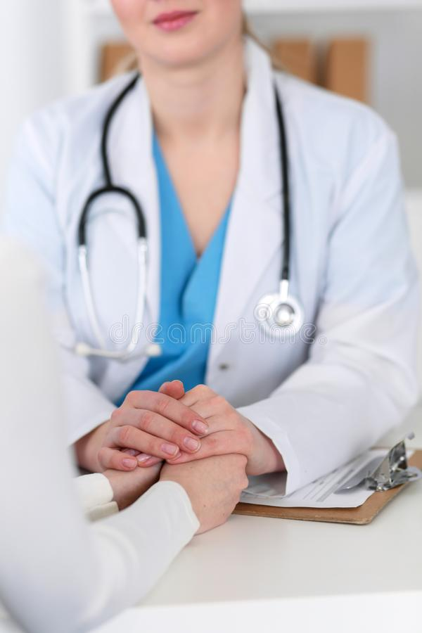 Medicine doctor hand reassuring her female patient closeup. Medicine, comforting and trusting concept in health care royalty free stock photo