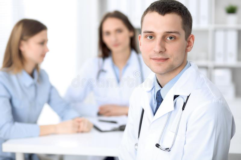 Medicine doctor standing and smiling on the background with patient in the bed royalty free stock images