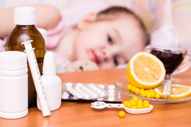Medicine e vitamine sulla tavola contro lo sfondo di un bambino in un letto che ha varicella immagine stock libera da diritti