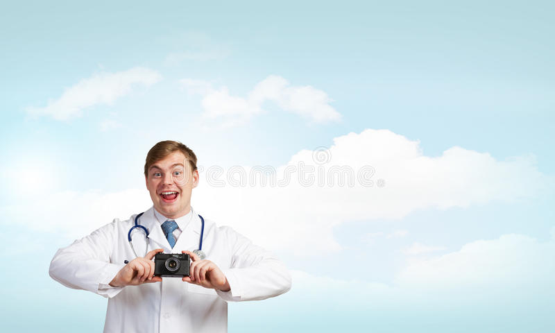 Medicine exploration. Funny young doctor with photo camera screaming emotionally royalty free stock photos