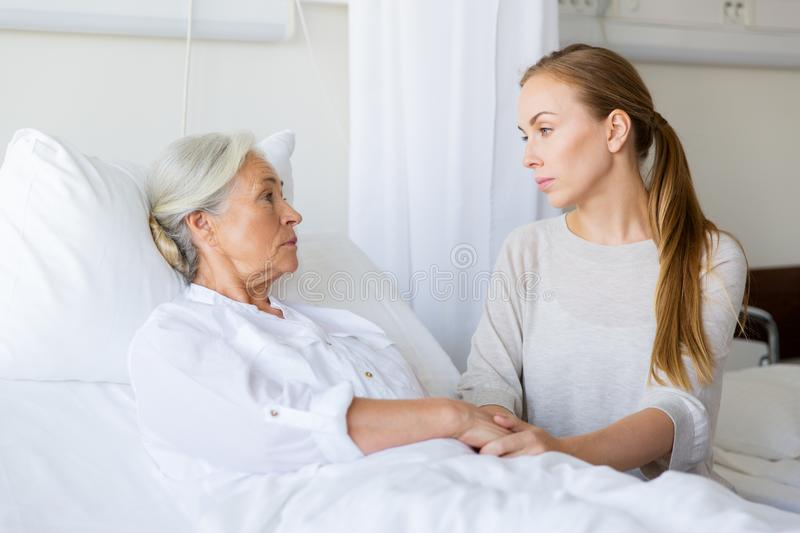 Daughter visiting her senior mother at hospital. Medicine, family, healthcare and people concept - daughter visiting and cheering her mother lying in bed at royalty free stock photos