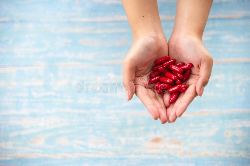 Medicine, healthcare, concept. Closed up hands hold the red medicines or vitamines on the wooden background. Medicine, healthcare, concept. Closed up hands hold royalty free stock images