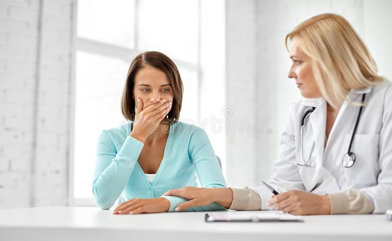 Doctor and sad woman patient at hospital royalty free stock photography
