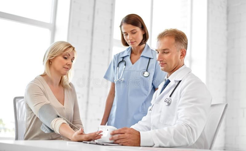Doctor measuring patient woman`s blood pressure stock photo