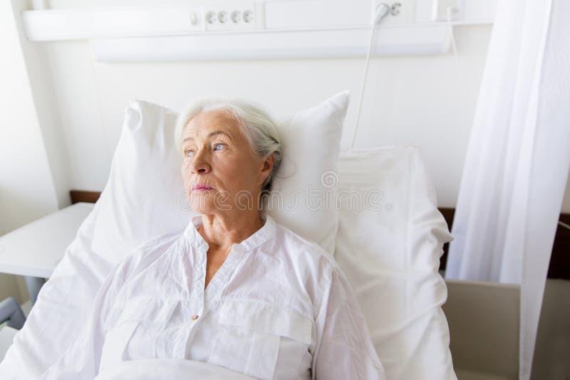 Sad senior woman lying on bed at hospital ward. Medicine, healthcare and old people concept - sad senior woman lying on bed at hospital ward royalty free stock photo