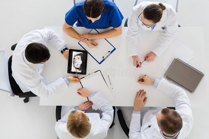 Doctors with jaw x-ray on tablet pc at clinic royalty free stock image