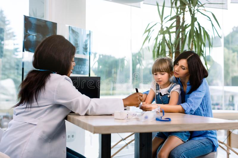 Medicine, healthcare and pediatry concept - african american doctor giving treatment recommendations for caucasian stock photo