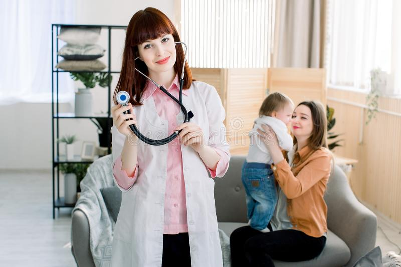 Medicine, healthcare, pediatry and people concept - Attractive female doctor in front of woman with baby, doctor`s visit stock images