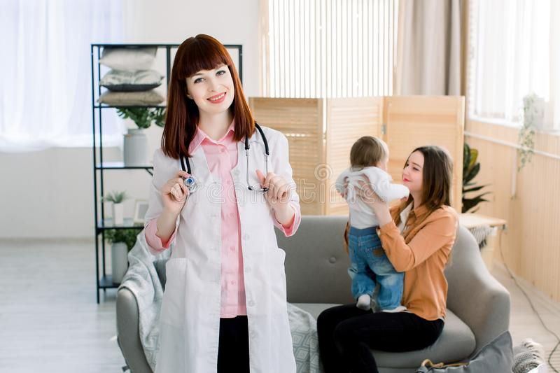 Medicine, healthcare, pediatry and people concept - woman with baby sitting on the sofa, and young pretty woman doctor royalty free stock images