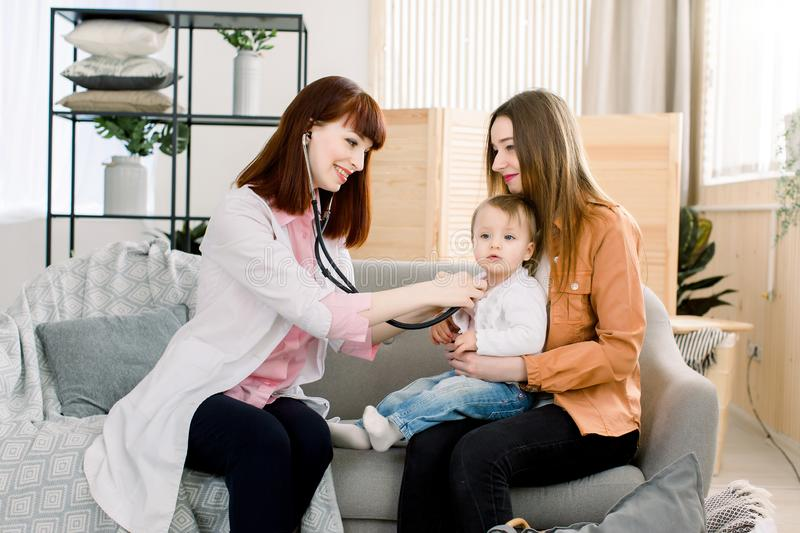 Medicine, healthcare, pediatry and people concept - Young woman Pediatrician checks breath stethoscope a little girl in stock photography