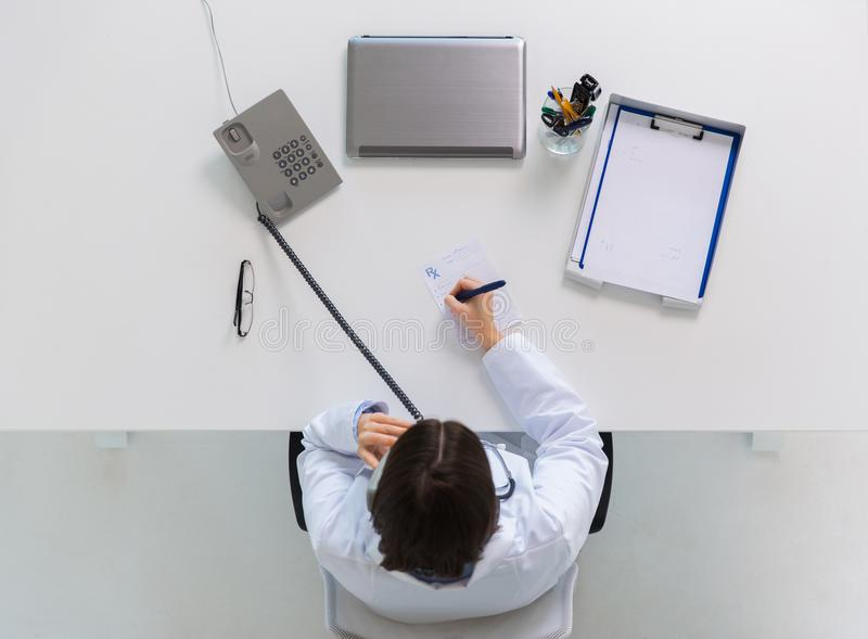 Doctor with prescription calling on phone. Medicine, healthcare and people concept - doctor with prescription calling on phone at table in clinic stock images