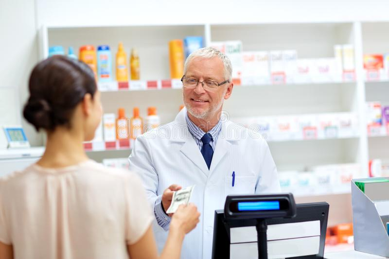 Customer giving money to pharmacist at drugstore stock photo