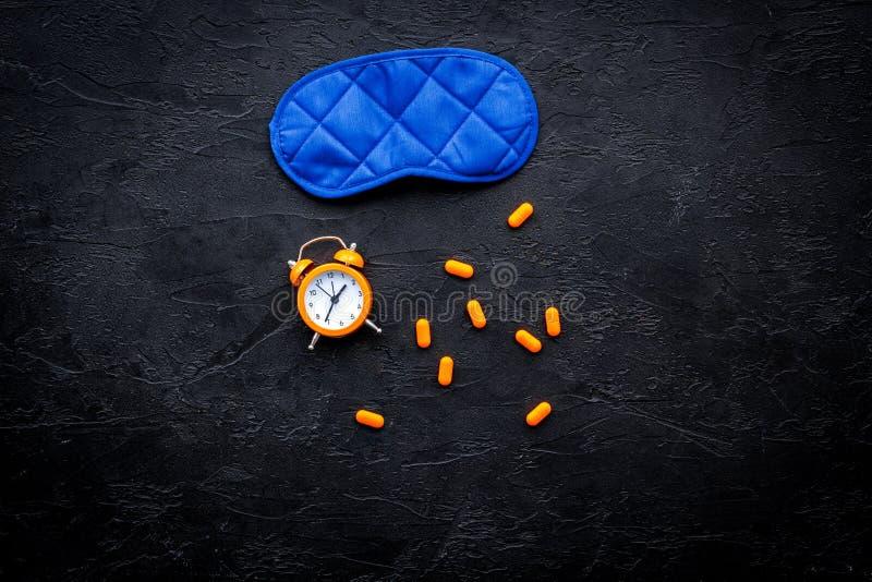 Medicine helps get asleep. Good sleep. Sleeping pills near sleeping mask and alarm clock on black background top view.  stock photo