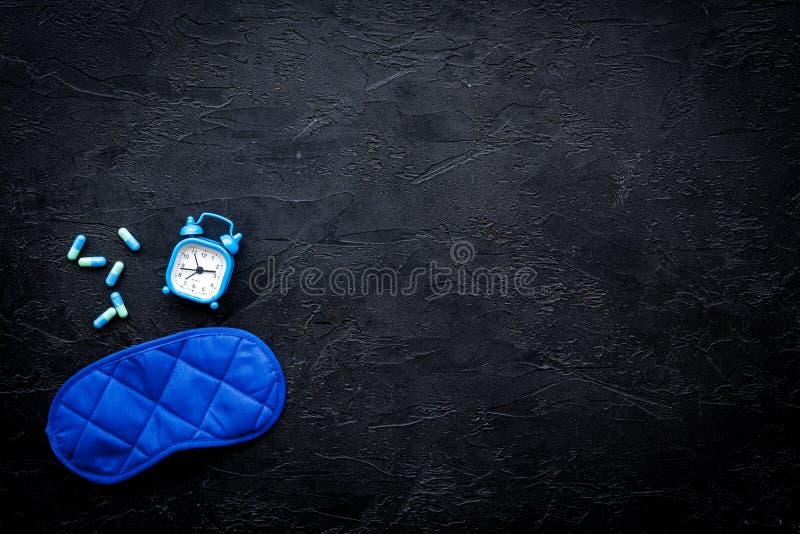 Medicine helps get asleep. Good sleep. Sleeping pills near sleeping mask and alarm clock on black background top view.  royalty free stock photo