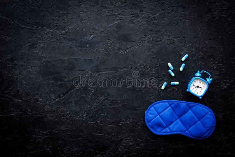 Medicine helps get asleep. Good sleep. Sleeping pills near sleeping mask and alarm clock on black background top view.  stock photography