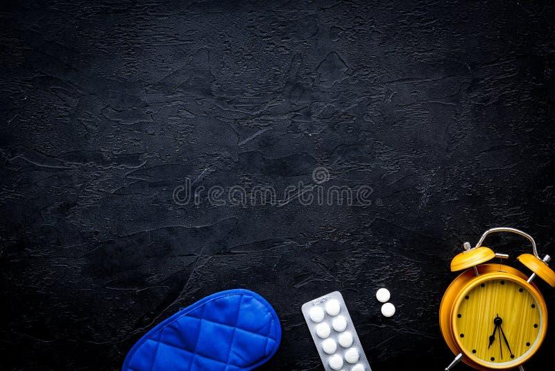Medicine helps get asleep. Good sleep. Sleeping pills near sleeping mask and alarm clock on black background top view.  royalty free stock images
