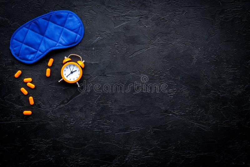 Medicine helps get asleep. Good sleep. Sleeping pills near sleeping mask and alarm clock on black background top view.  royalty free stock photos
