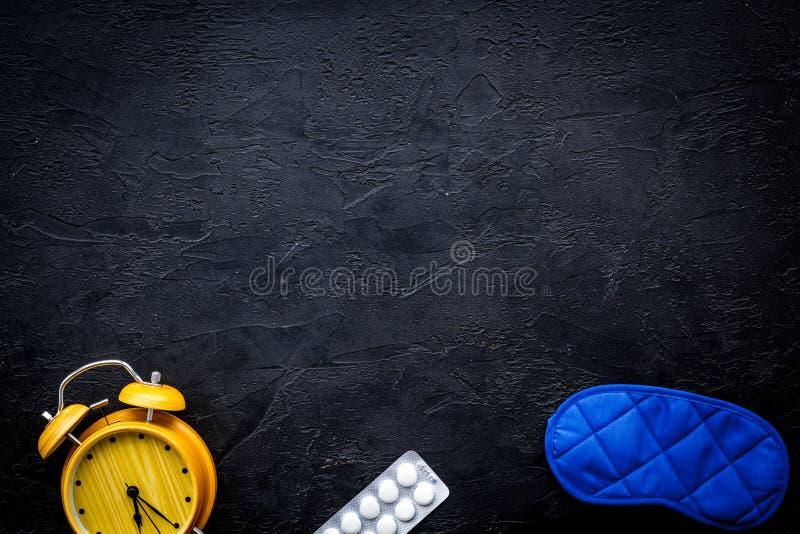 Medicine helps get asleep. Good sleep. Sleeping pills near sleeping mask and alarm clock on black background top view.  stock images