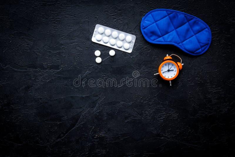 Medicine helps get asleep. Good sleep. Sleeping pills near sleeping mask and alarm clock on black background top view.  royalty free stock photography