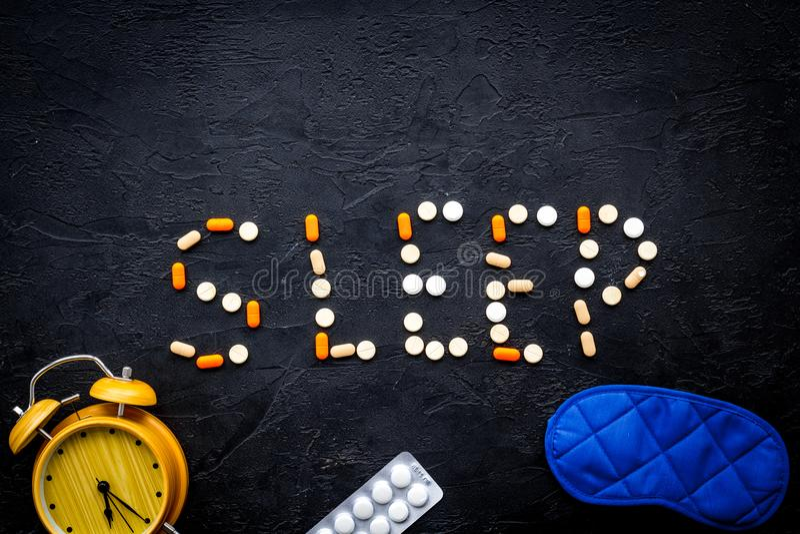 Medicine helps get asleep. Good sleep. Word sleep lined with sleeping pills near sleeping mask and alarm clock on black. Background top view stock photos
