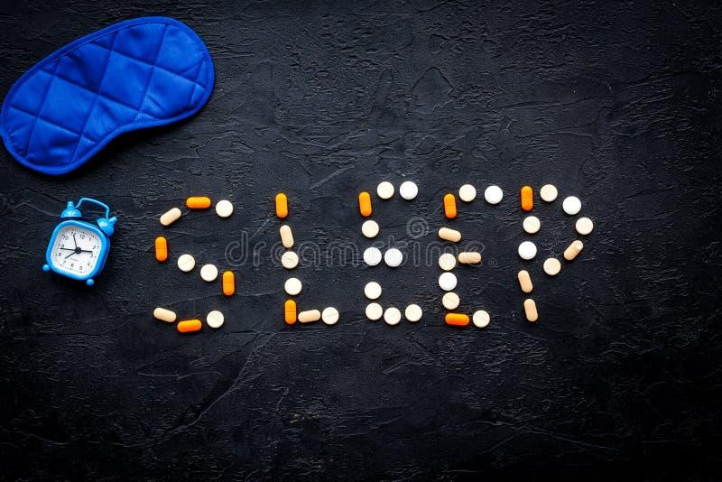 Medicine helps get asleep. Good sleep. Word sleep lined with sleeping pills near sleeping mask and alarm clock on black. Background top view stock photo