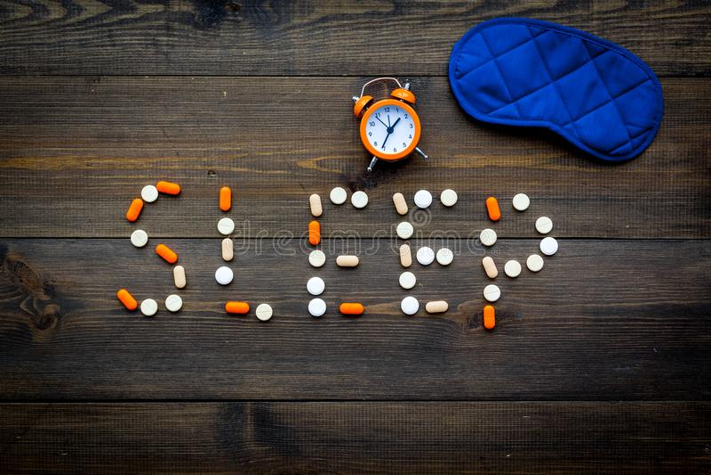 Medicine helps get asleep. Good sleep. Word sleep lined with sleeping pills near sleeping mask and alarm clock on dark. Wooden background top view stock images