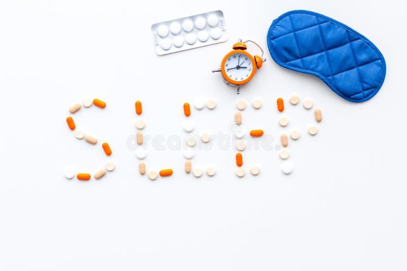 Medicine helps get asleep. Good sleep. Word sleep lined with sleeping pills near sleeping mask and alarm clock on white. Wooden background top view stock photos