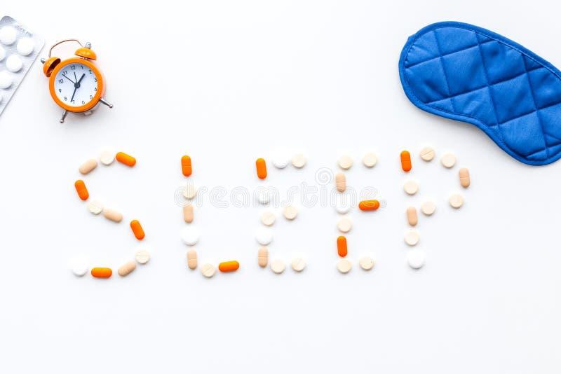 Medicine helps get asleep. Good sleep. Word sleep lined with sleeping pills near sleeping mask and alarm clock on white. Wooden background top view stock photo