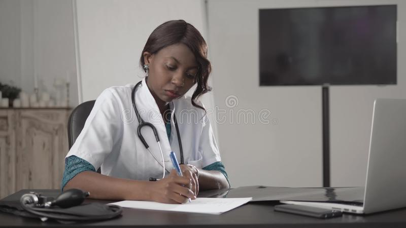 Medicine, people and healthcare concept - happy female african american doctor or nurse writing medical report to stock images