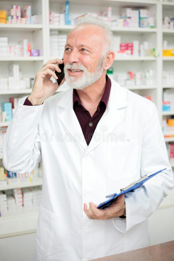 Senior male pharmacist talking on the phone and holding a clipboard stock image